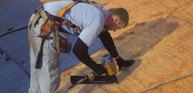 Older man on a roof installing shingles